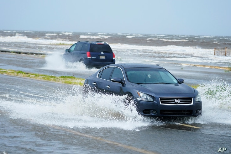 Cars drive through flood waters along route 90 as outer bands of Hurricane Ida arrive Sunday, Aug. 29, 2021, in Gulfport, Miss...
