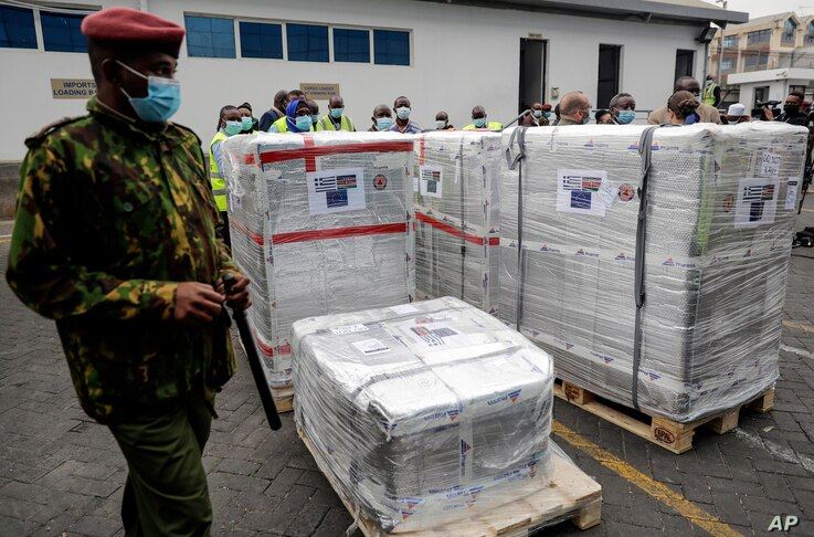 FILE - In this file Friday, Aug.6. 2021 file photo, a Kenyan soldier guards a consignment of 182,000 AstraZeneca vaccines from…
