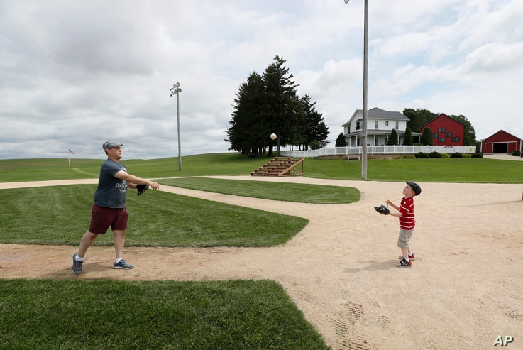Jeremiah Bronson, of Ames, Iowa, plays catch with his sone Ben, right, on the field at the Field of Dreams movie site, Friday,…