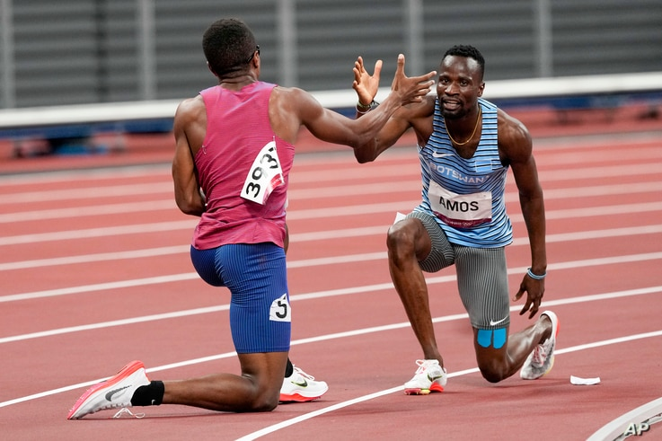 Isaiah Jewett, of the United States, and Nijel Amos, right, of Botswana, shake hands after falling in the men's 800-meter…