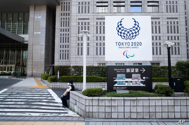 A security guard takes a break in front of the Tokyo metropolitan building during a Paralympic torch relay event in Tokyo,…