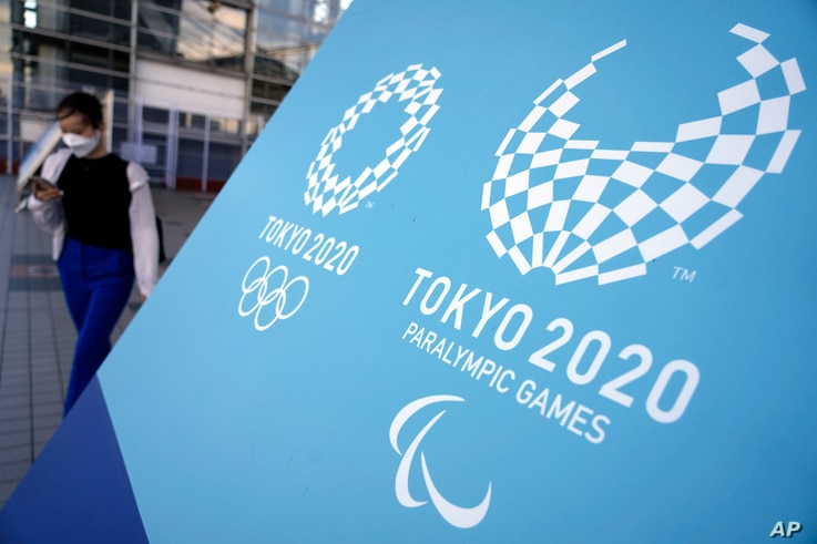 A woman walks near a sing of the Tokyo 2020 Olympic and Paralympic Games, Friday, Aug. 20, 2021, in Tokyo. The Tokyo…