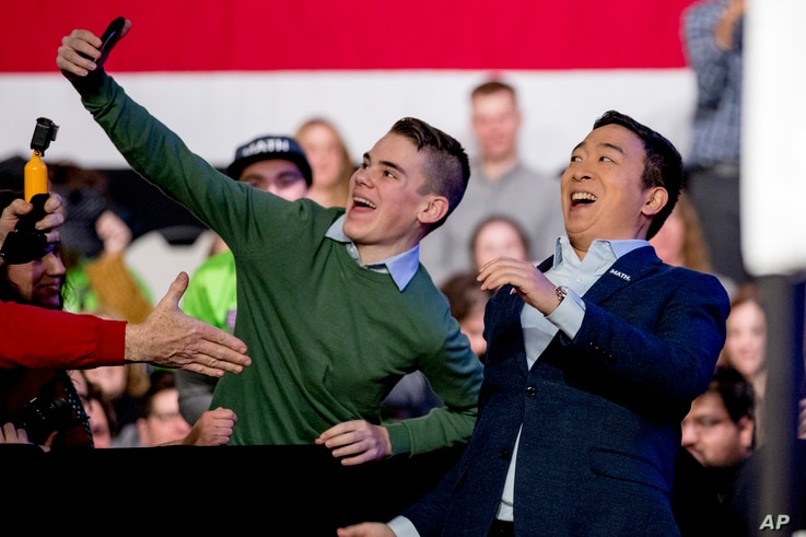 Democratic presidential candidate Andrew Yang takes a photograph with a member of the audience as he arrives at 'Our Rights,...