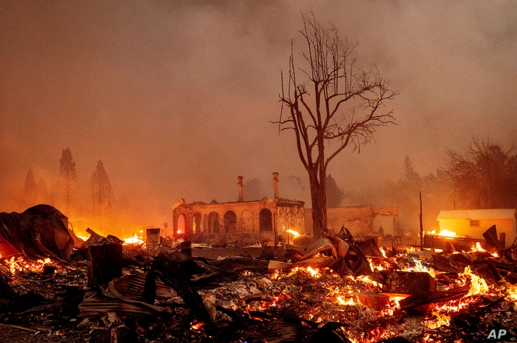 Buildings burn as the Dixie Fire tears through the Greenville community of Plumas County, Calif., on Wednesday, Aug. 4, 2021…
