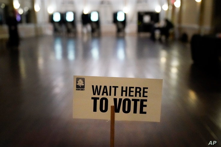 A sign is displayed for voters to guide the way at a precinct during Georgia's Senate runoff elections on Tuesday, Jan. 5, 2021...