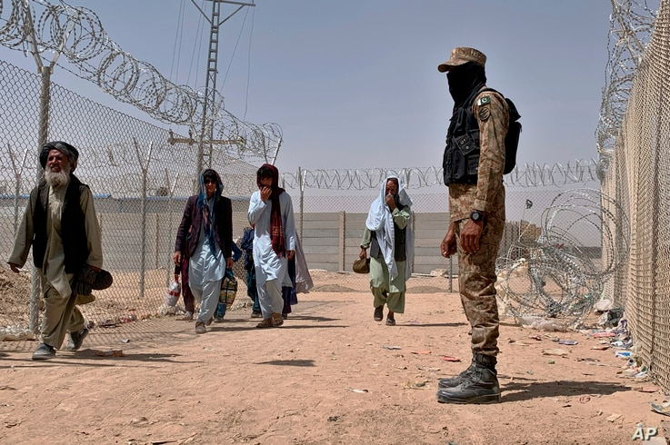 FILE - In this Aug. 20, 2021, file photo, Pakistani army soldier stands guard while Afghan people enter into Pakistan through a…