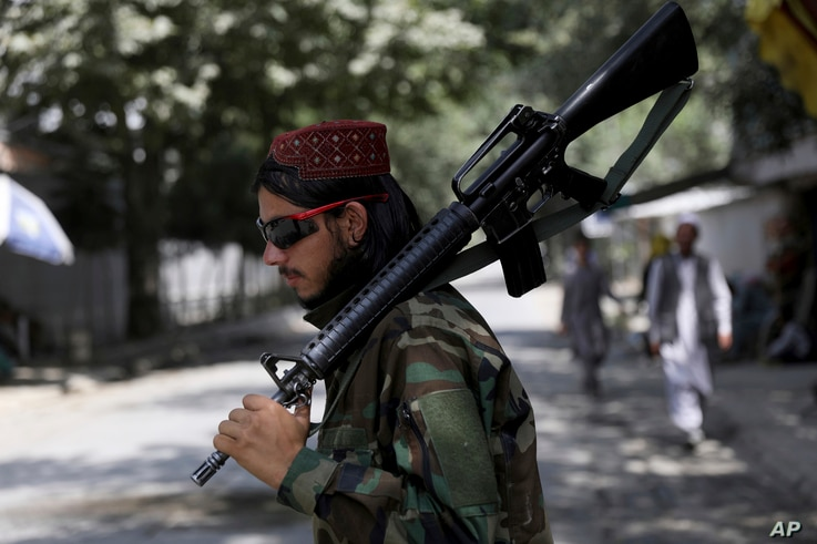 A Taliban fighter stands guard at a checkpoint in the Wazir Akbar Khan neighborhood in the city of Kabul, Afghanistan, Sunday,…