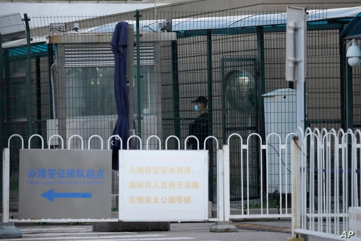 A security guard stands guard behind fences around the U.S. embassy near a sign board directing visa applicants in Beijing on...