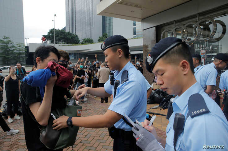 A police officer checks the bag of a pedestrian following a day of violence over an extradition bill that would allow people to be sent to mainland China for trial, in Hong Kong, China June 13, 2019.