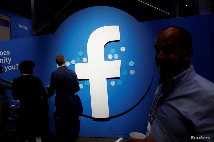 FILE - Attendees walk past a Facebook logo during Facebook Inc's F8 developers conference in San Jose, California, United States.