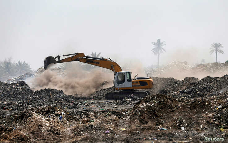 A municipal worker drives a shovel machine to extinguish a fire inside the garbage at a rubbish dump in Baghdad