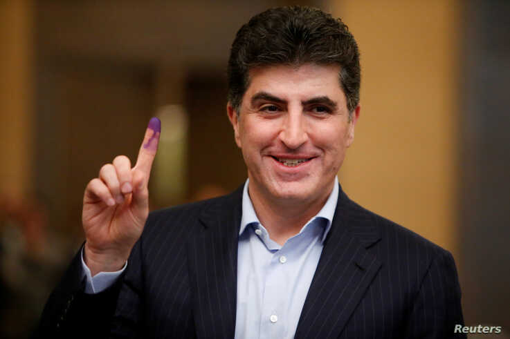 FILE - Kurdistan Regional Government Prime Minister Nechirvan Barzani shows his ink-stained finger after casting his vote at a polling station during the parliamentary election in Erbil
