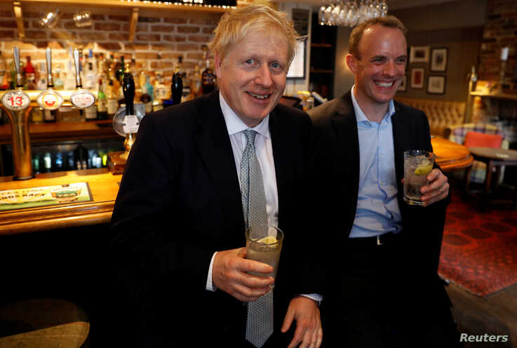 Boris Johnson, a leadership candidate for Britain's Conservative Party, and Britain's former Brexit Minister Dominic Raab visit a pub in Oxshott