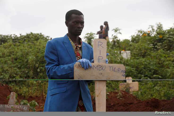FILE - A Congolese man holds a cross during the burial service of Congolese woman Kahambu Tulirwaho who died of Ebola, at a cemetery in Butembo.