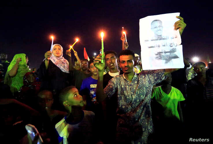 Sudanese protesters hold candles near a portrait of a civilian killed in march during a demonstration to commemorate 40 days since the sit-in massacre in Khartoum North