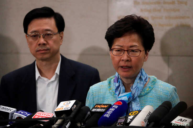 Hong Kong Chief Executive Carrie Lam, right, and Secretary for Security John Lee Ka-chiu speak to media over an extradition bill in Hong Kong, July 2, 2019.