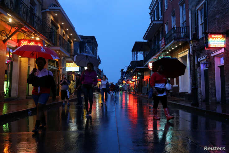 Tourists walk on Bourbon Street during Hurricane Barry in New Orleans, La.,  July 13, 2019.
