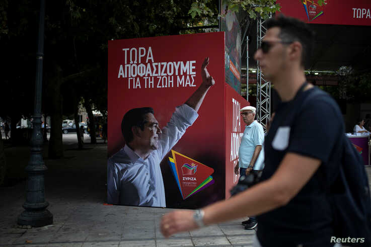 People walk past a poster depicting Greek PM Tsipras at the election kiosk of the leftist Syriza party in Athens