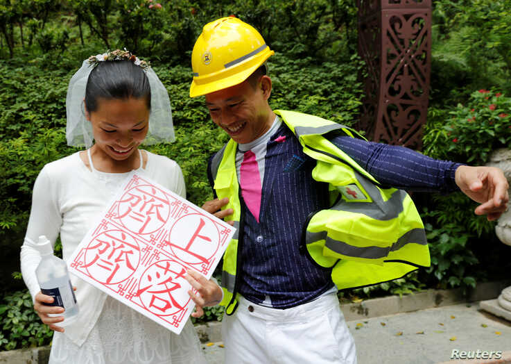 """Henry Tong, wearing a helmet and a first aid vest associated with the anti-extradition bill protests, poses for pictures with his wife, Elaine To, after getting married in Hong Kong, Aug. 4, 2019. The placard reads,""""Let's go for it together."""""""