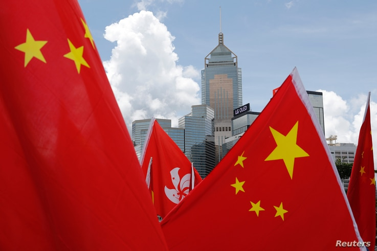 Buildings are seen above Hong Kong and Chinese flags, as pro-China supporters celebration after China's parliament passes national security law for Hong Kong, in Hong Kong