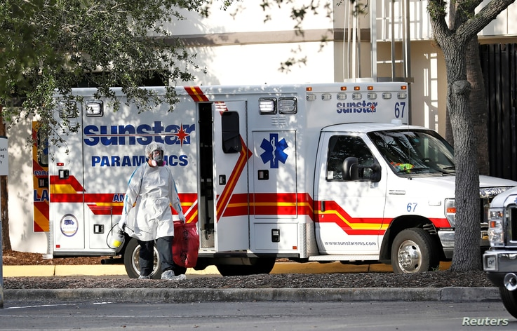 A paramedic dressed in personal protective equipment exits an ambulance at St. Petersburg General Hospital in Florida