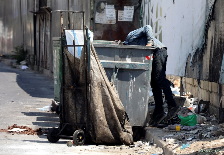 FILE PHOTO: A man searches through a garbage bin in Beirut