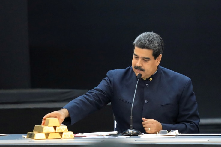 FILE PHOTO: Venezuela's President Maduro touches a gold bar as he speaks during a meeting with the ministers responsible for the economic sector in Caracas