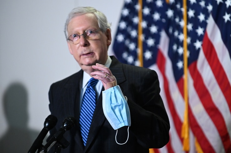 Senate Majority Leader McConnell holds a face mask while participating in a news conference at the U.S. Capitol in Washington