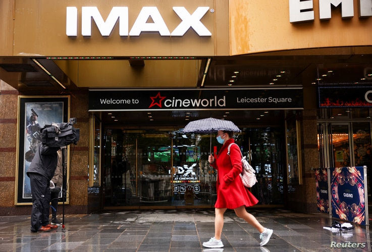 A woman holds an umbrella as she walks past a Cineworld in Leicester's Square in London