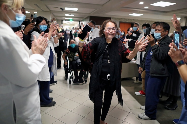 Intensive Care Unit Nurse Merlin Pambuan, is cheered by hospital staff as she walks out of the hospital in Long Beach