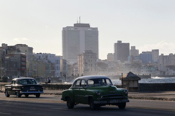 Vintage cars drive on the seafront boulevard El Malecon in Havana