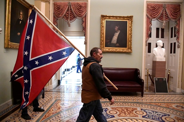 A supporter of President Donald Trump carries a Confederate battle flag on the second floor of the U.S. Capitol after breaching security, in Washington, Jan. 6, 2021.
