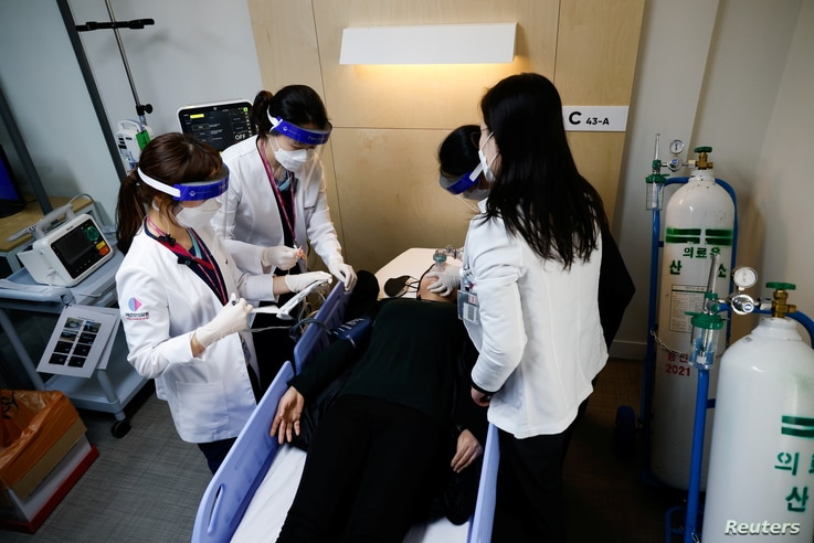 Nurses take part in the coronavirus disease (COVID-19) vaccination mock drill at a first aid facility of the COVID-19 vaccination center in Seoul