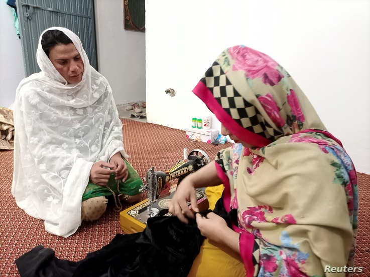 Rani Khan looks at one of her students during a tailoring lesson in Islamabad