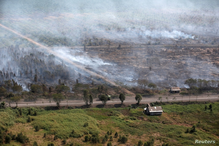 FILE PHOTO: Wooden houses are pictured as smoke from forest fires envelops trees near Banjarmasin in South Kalimantan province, Indonesia