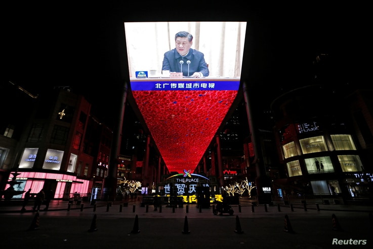 Giant screen shows CCTV state media broadcast of Chinese President Xi Jinping, at a shopping complex in Beijing