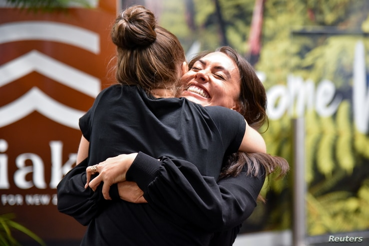 Families and loved ones embrace after arriving on the first Air New Zealand flight to land as quarantine-free travel between Australia and New Zealand begins, in Wellington