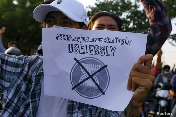 A protester against Myanmar's junta holds a placard criticising the Association of Southeast Asian Nations (ASEAN), in Mandalay