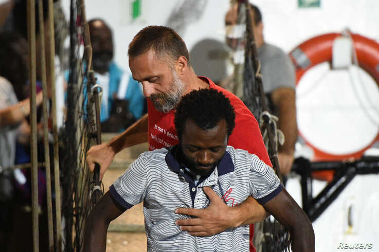 A migrant is helped off the Spanish rescue ship Open Arms NGO, as it arrives in Lampedusa, Italy, August 20, 2019. REUTERS/Guglielmo Mangiapane