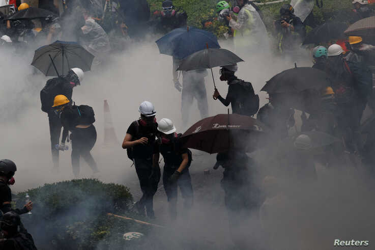 Anti-extradition bill protesters are surrounded by tear gas during clashes with police in Tsuen Wan in Hong Kong, Aug. 25, 2019.