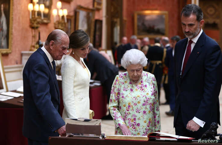 FILE - Britain's Queen Elizabeth II, Prince Philip, Duke of Edinburgh and Spain's King Felipe and Queen Letizia look at a display of Spanish items from the Royal Collection at Buckingham Palace, London, July 12, 2017.