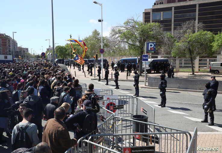 Catalan police stand guard in front of demonstrators during a protest outside a building where Spain's King Felipe was attending a ceremony in Barcelona, Spain, April 9, 2018.