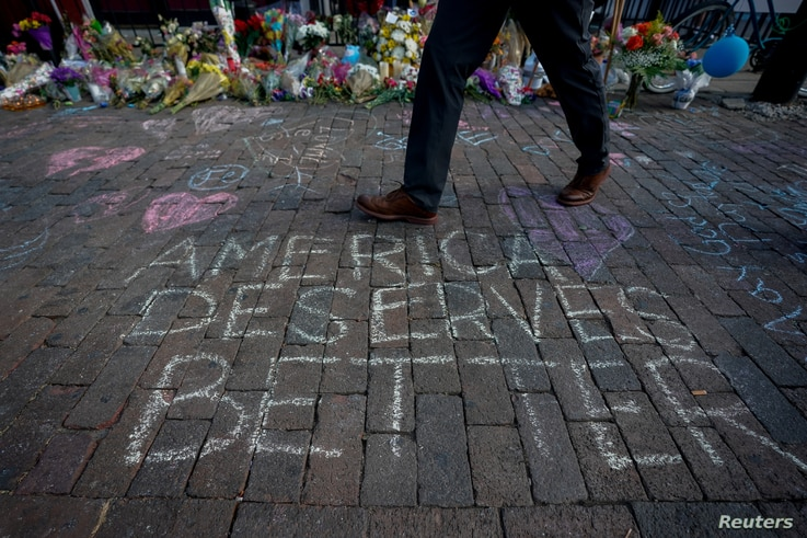 A man walks past a memorial for those killed in a mass shooting in Dayton, Ohio, U.S. August 7, 2019.  REUTERS/Bryan Woolston