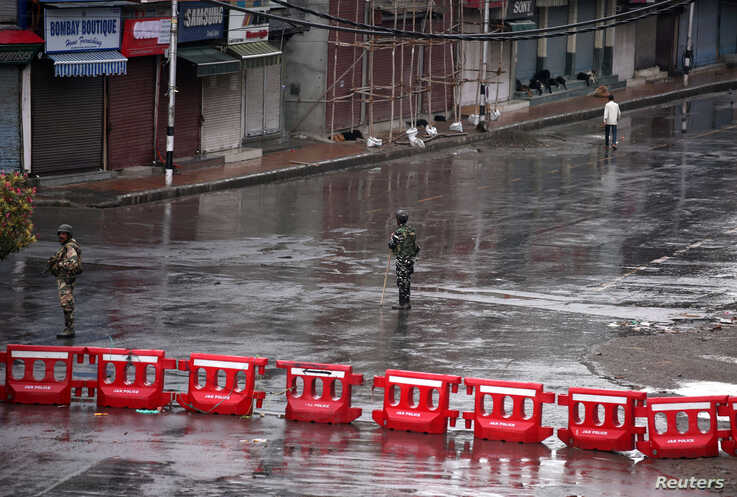 Indian security force personnel stand guard in a deserted street during restrictions after the government scrapped special status for Kashmir, in Srinagar August 8, 2019. REUTERS/Danish Ismail