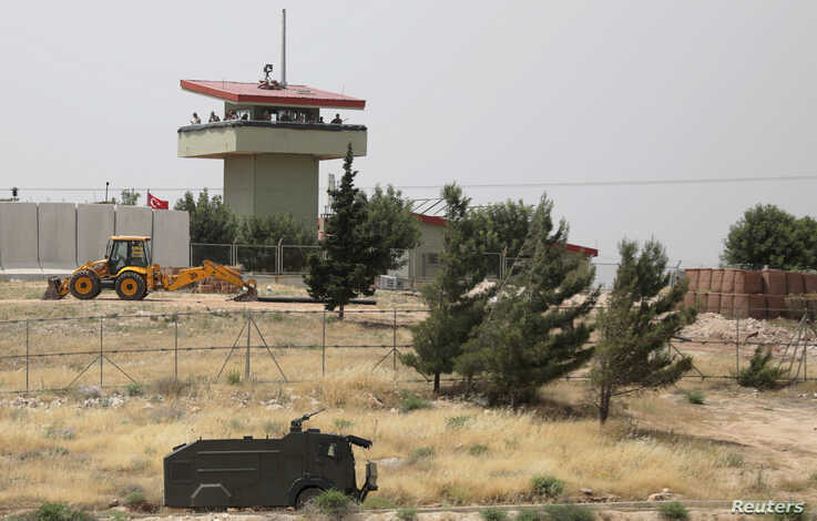 FILE PHOTO: Turkish soldiers stand on a watchtower at the Atmeh crossing on the Syrian-Turkish border, as seen from the Syrian side, in Idlib governorate, Syria, May 31, 2019. REUTERS/Khalil Ashawi/File Photo