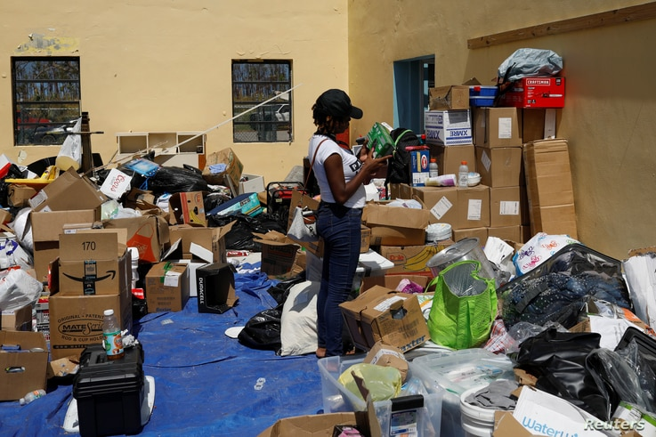 A volunteer looks for supplies at an airport during an evacuation operation after Hurricane Dorian hit the Abaco Islands in Treasure Cay, Bahamas, September 7, 2019. REUTERS/Marco Bello