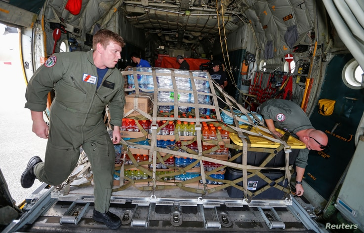 U.S. Coast Guard Petty Officers Nicholas Eudier (L) and Nate Matthews unload relief supplies for Hurricane Dorian victims from their C-130 aircraft  in Andros, Bahamas September 7, 2019. REUTERS/Joe Skipper