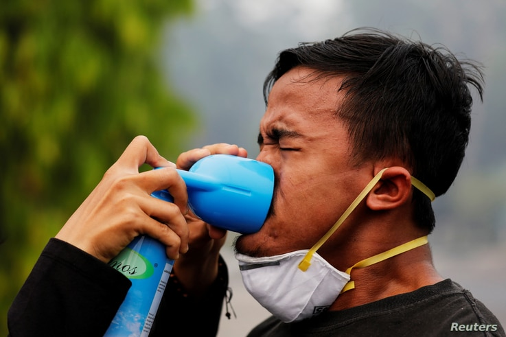 A youth inhales an oxygen-can as he being treatmented during a Global Climate Strike rally as smog covers the city due to the forest fires in Palangka Raya, Central Kalimantan province, Indonesia, September 20, 2019. REUTERS/Willy Kurniawan