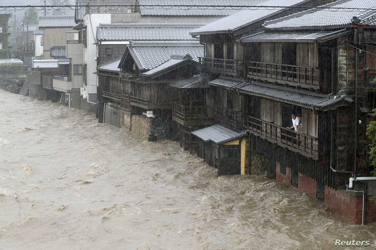 Men watch the swollen Isuzu River due to heavy rain caused by Typhoon Hagibis in Ise, central Japan, in this photo taken by…
