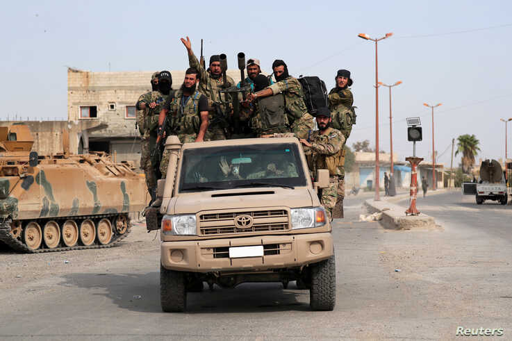 Turkey-backed Syrian rebel fighters ride on a vehicle at the border town of Tel Abyad, Syria